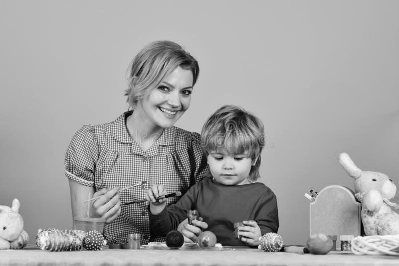 La famiglia prepara per la festa Uova della pittura del figlio e della madre fotografie stock