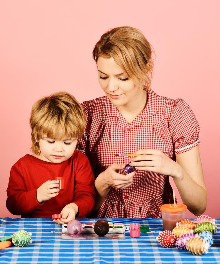 La famiglia prepara per la festa Uova della pittura del figlio e della madre fotografia stock