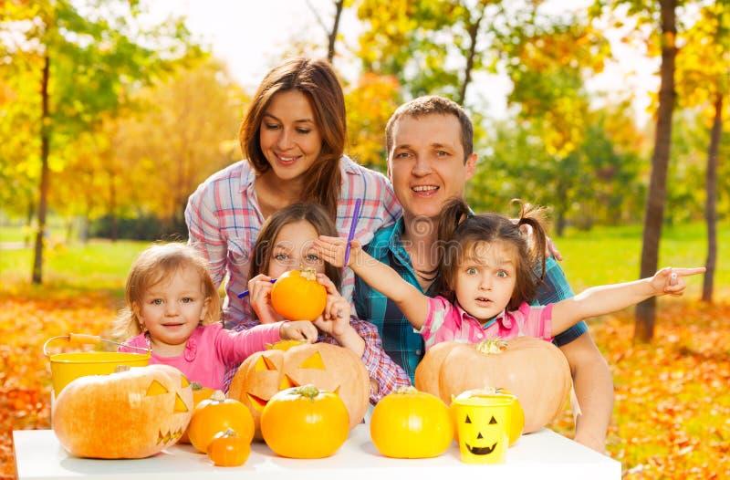 La famiglia scolpisce le zucche per Halloween nel giardino fotografie stock