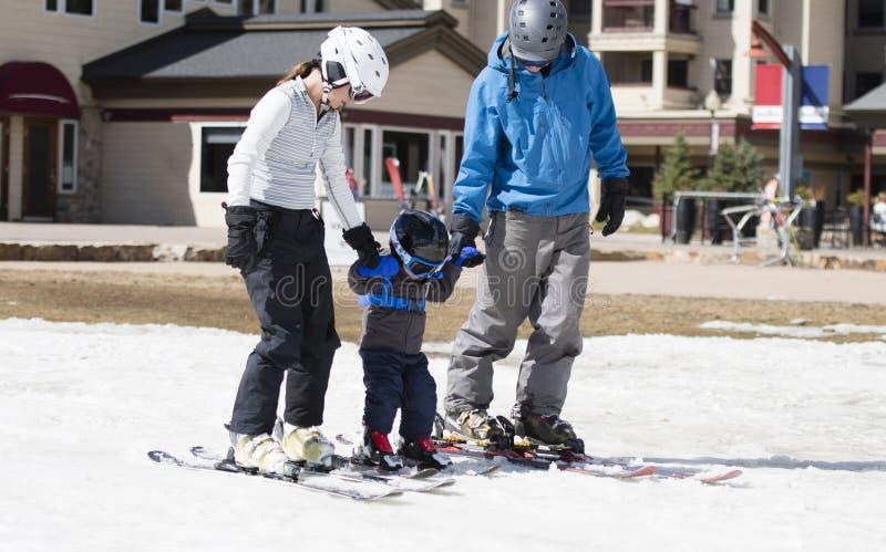 La famiglia si prepara per sciare con il ragazzo del bambino Tutti vestiti sicuro con i caschi immagini stock libere da diritti