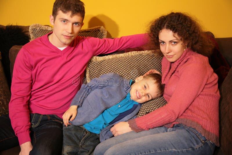 La famiglia si siede sul sofà immagine stock libera da diritti