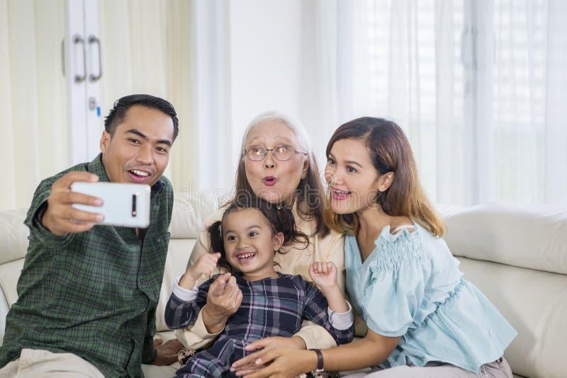 La famiglia sorridente della generazione tre prende il selfie a casa fotografia stock
