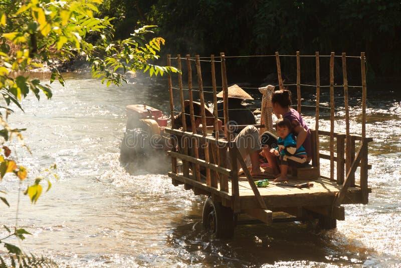 La famiglia sta attraversando un fiume con il loro traktor immagini stock libere da diritti