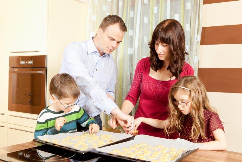 La famiglia sta cocendo i biscotti immagini stock