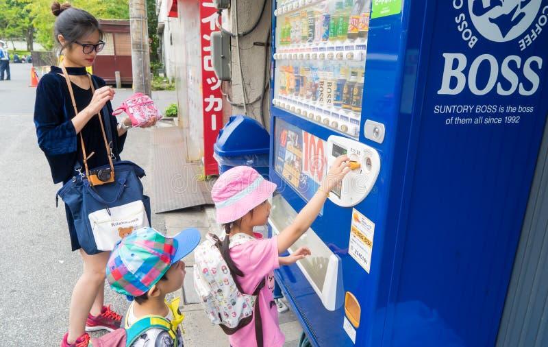 La famiglia sta comprando le latte della bibita dai venditori della moneta fotografia stock libera da diritti