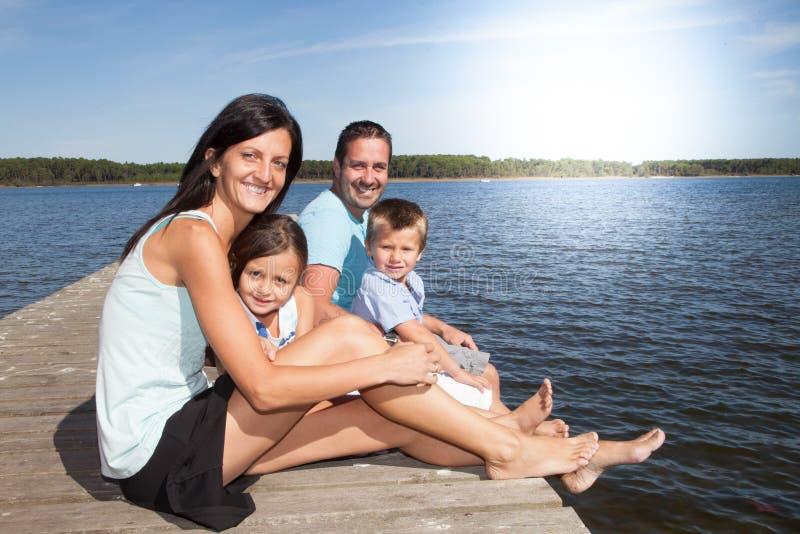 la famiglia sulla vacanza ha molto divertimento e l'amore si rilassa sul pontone di legno immagini stock