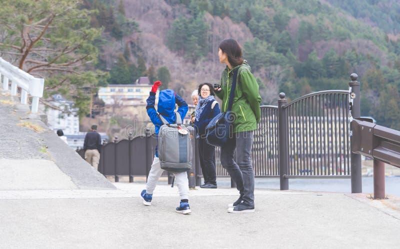 La famiglia turistica sta camminando sul lago Kawaguchiko fotografia stock libera da diritti