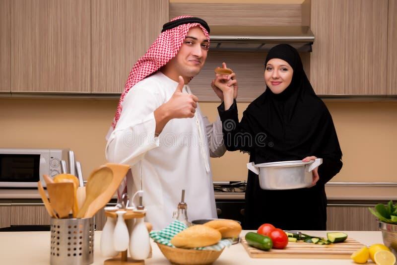 La familia árabe joven en la cocina imagenes de archivo