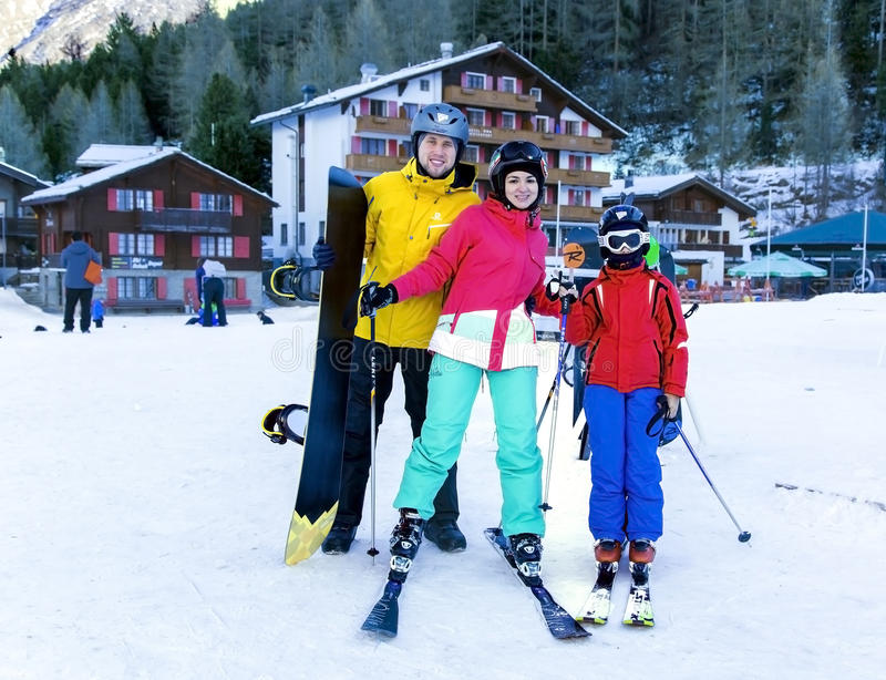 La familia activa joven disfruta de deportes de invierno en el centro turístico suizo encantador de la Saas-tarifa fotografía de archivo libre de regalías