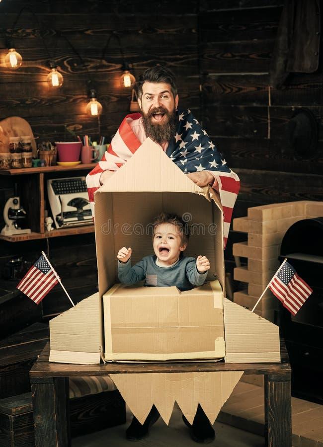 La familia alegre americana con los E.E.U.U. señala el juego por medio de una bandera con el cohete hecho fuera de la caja de car foto de archivo libre de regalías