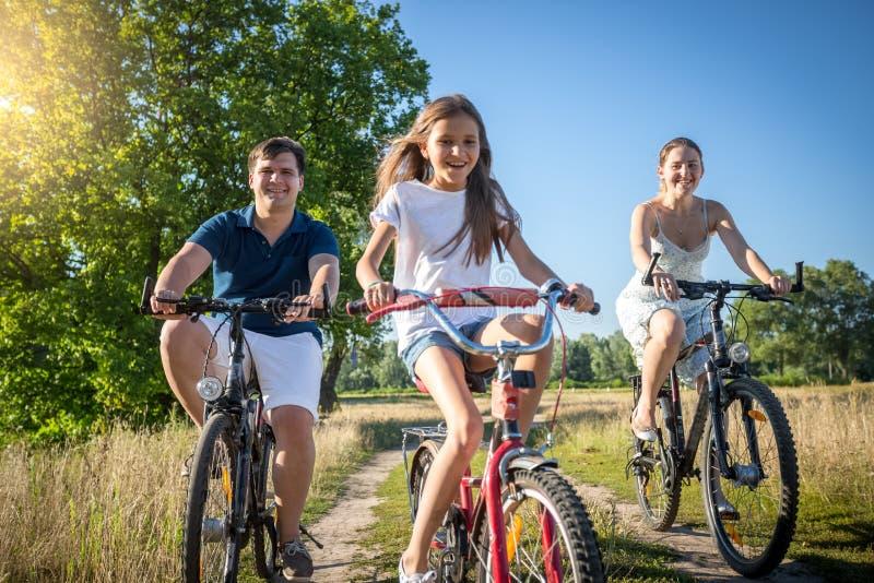 La familia alegre con el montar a caballo de la hija monta en bicicleta en prado en soleado foto de archivo libre de regalías