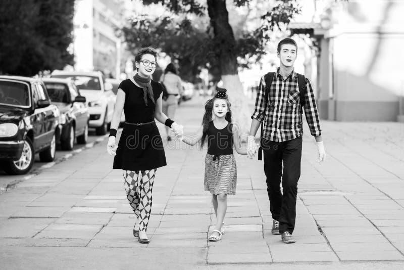 La familia alegre de imita llevando a cabo las manos que camina abajo de la calle fotografía de archivo