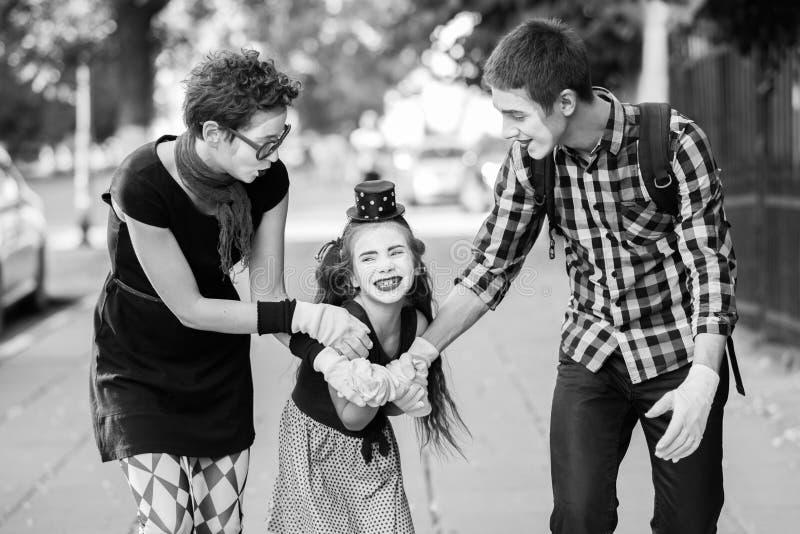 La familia alegre de imita llevando a cabo las manos que camina abajo de la calle fotografía de archivo libre de regalías