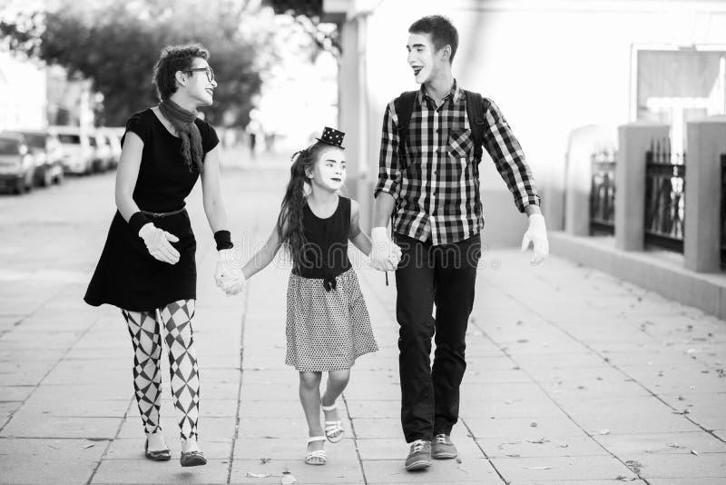 La familia alegre de imita llevando a cabo las manos que camina abajo de la calle imagenes de archivo