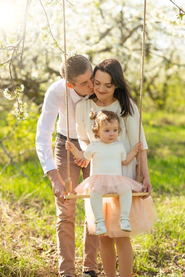 La familia alegre sacude a un niño en un oscilación, en un jardín florecido o un parque Con gusto, humor del amor, de la primaver imagenes de archivo
