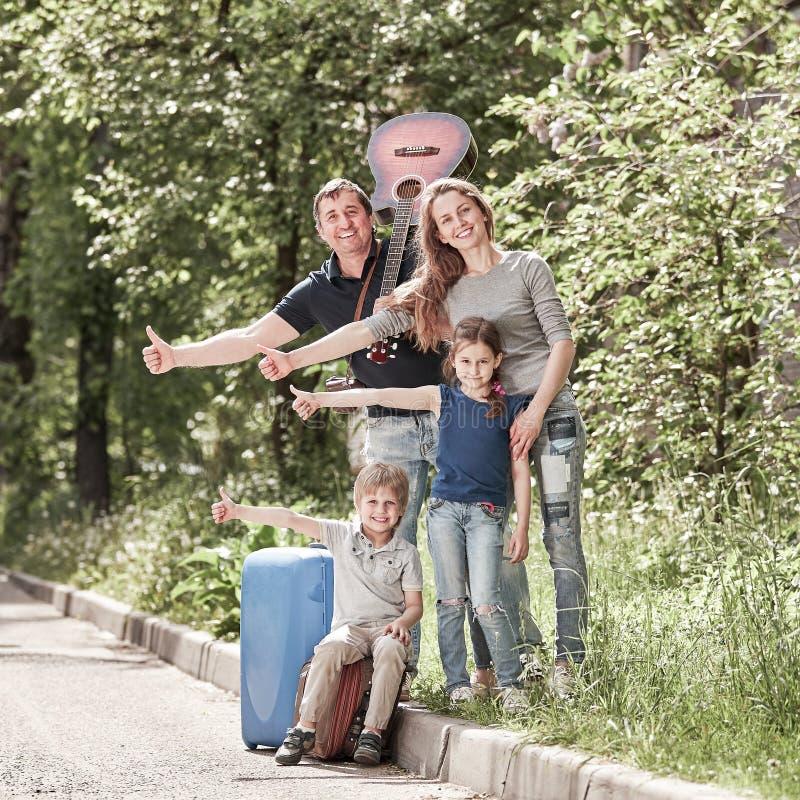 La familia alegre va en un viaje de autoestop fotografía de archivo libre de regalías