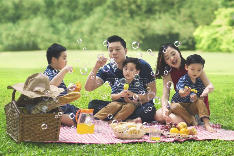 La familia asiática sopla el jabón de la burbuja en el parque fotografía de archivo