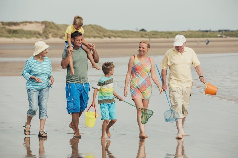 La familia camina a lo largo de la playa fotografía de archivo