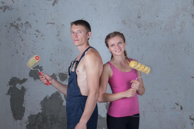 La familia cariñosa con la pintura de los rodillos repara en un apartamento foto de archivo