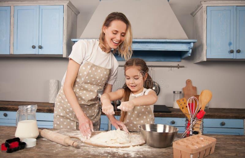 La familia cariñosa feliz está preparando la panadería junta La muchacha de la hija de la madre y del niño está haciendo las fotos de archivo libres de regalías