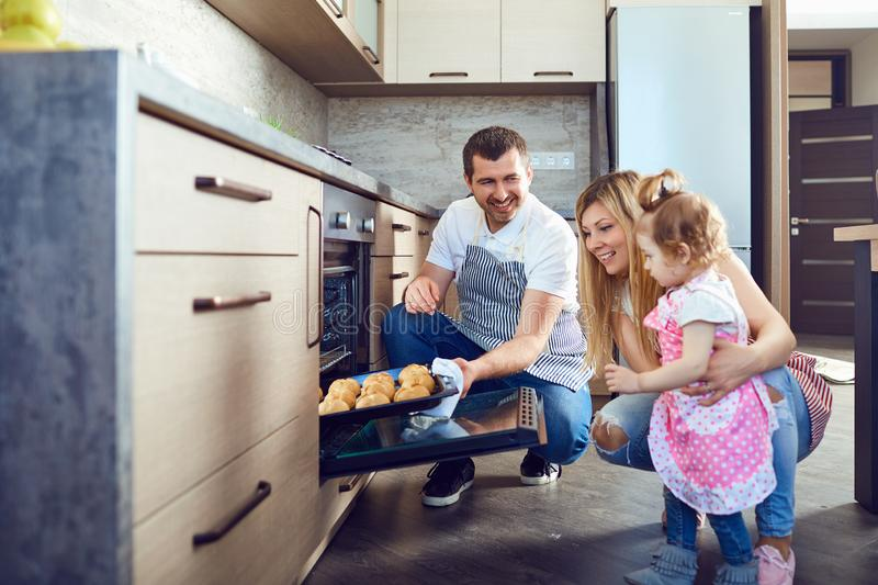 La familia cogerá una bandeja con las galletas del horno fotos de archivo libres de regalías