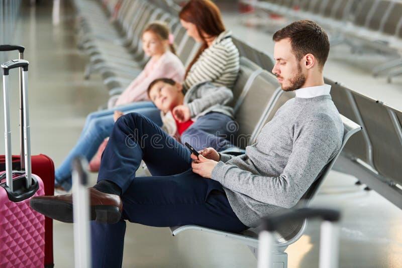 La familia con dos niños está esperando en el aeropuerto imagenes de archivo
