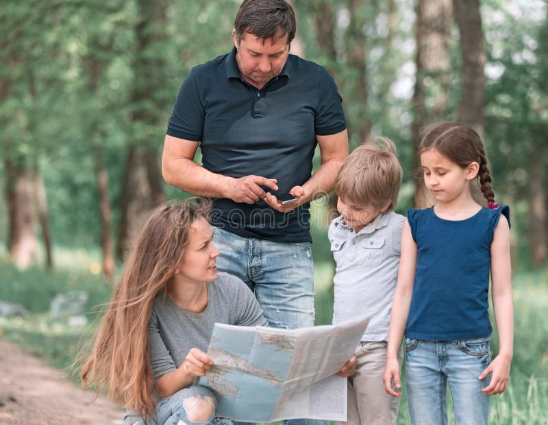 La familia con dos niños utiliza la tarjeta mientras que viaja fotografía de archivo libre de regalías