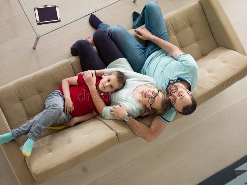 La familia con el niño pequeño goza en la sala de estar moderna imagenes de archivo