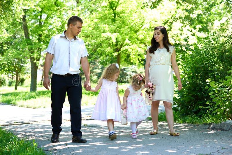 La familia con el niño y la mujer embarazada caminan en parque de la ciudad del verano fotografía de archivo libre de regalías