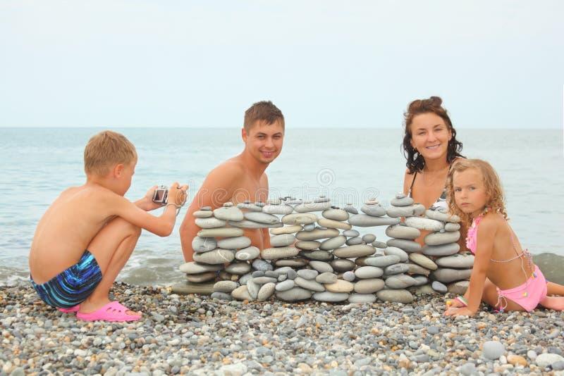 La familia con los niños acerca a la construcción de guijarros fotografía de archivo
