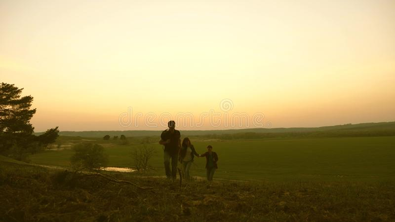 La familia con los niños viaja con las mochilas Familia feliz de turistas de vacaciones concepto del turismo de los deportes papá imagen de archivo libre de regalías
