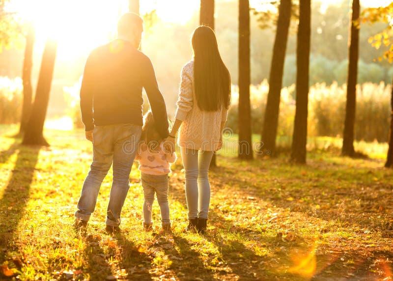 La familia con la pequeña hija pasa tiempo de la diversión en parque del otoño en su foto de archivo libre de regalías