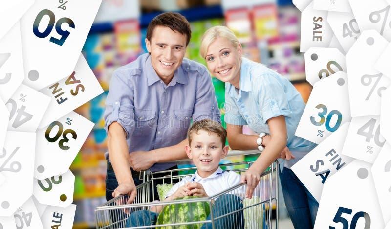 La familia conduce la carretilla de las compras con la comida foto de archivo libre de regalías