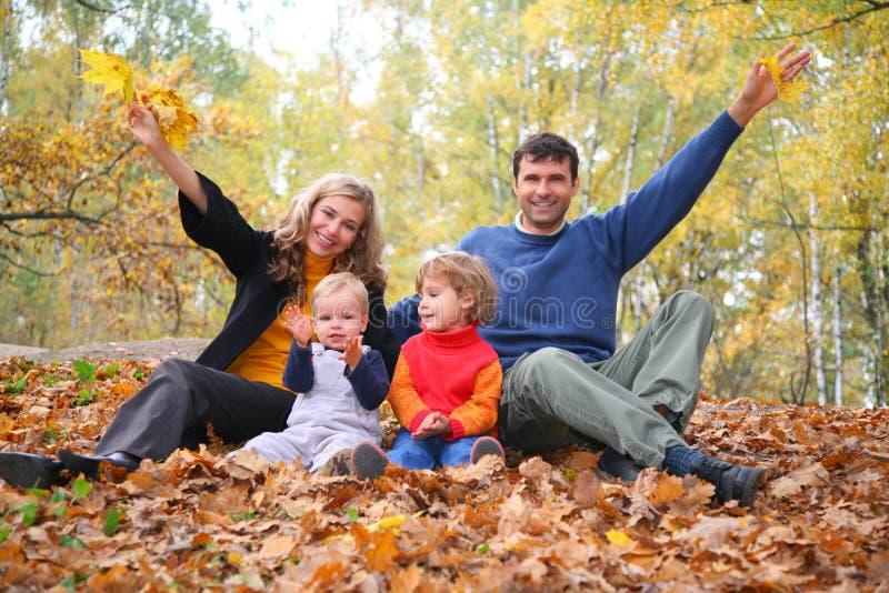 La familia de cuatro miembros se sienta en parque del otoño. fotos de archivo libres de regalías