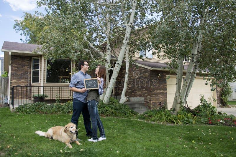 La familia de los pares y de perro delante de la nueva tenencia del hogar vendió la muestra y llaves de la pizarra foto de archivo