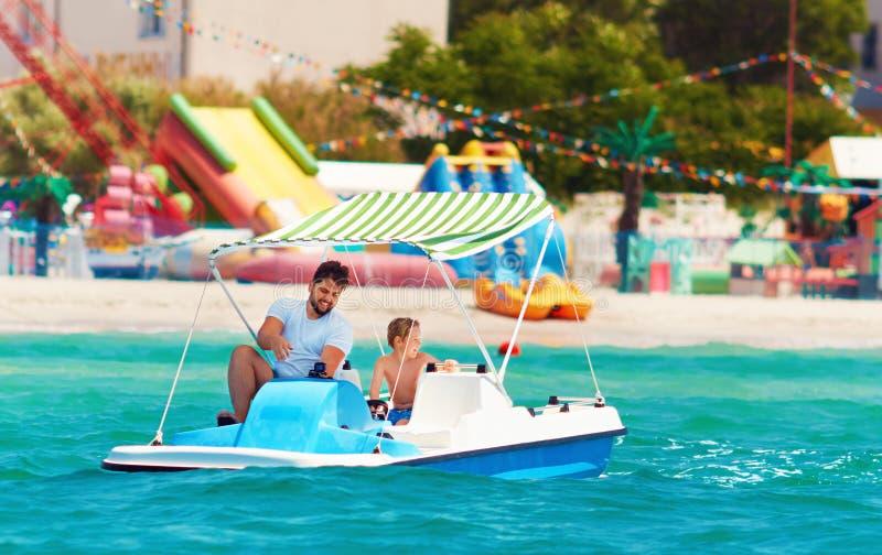 La familia, el padre y el hijo felices disfrutan de aventura del mar en el catamarán del watercraft en las vacaciones de verano fotos de archivo