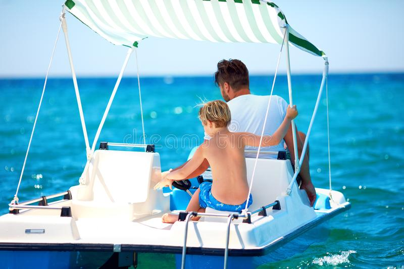 La familia, el padre y el hijo felices disfrutan de aventura del mar en el catamarán del watercraft en las vacaciones de verano imagen de archivo libre de regalías