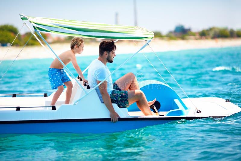 La familia, el padre y el hijo felices disfrutan de aventura del mar en el catamarán del watercraft en las vacaciones de verano fotografía de archivo