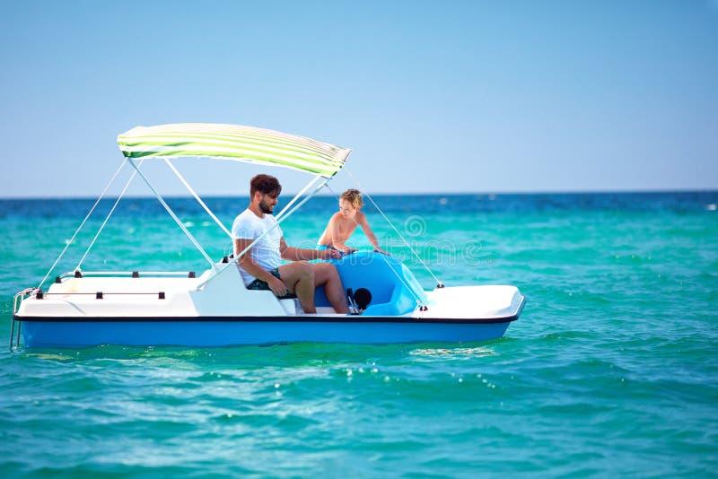 La familia, el padre y el hijo felices disfrutan de aventura del mar en el catamarán del watercraft en las vacaciones de verano foto de archivo