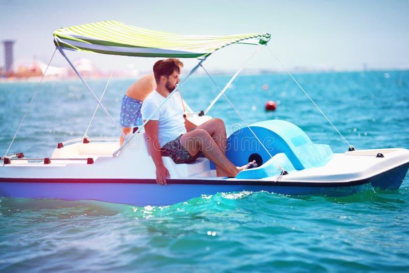 La familia, el padre y el hijo felices disfrutan de aventura del mar en el catamarán del watercraft en las vacaciones de verano foto de archivo libre de regalías