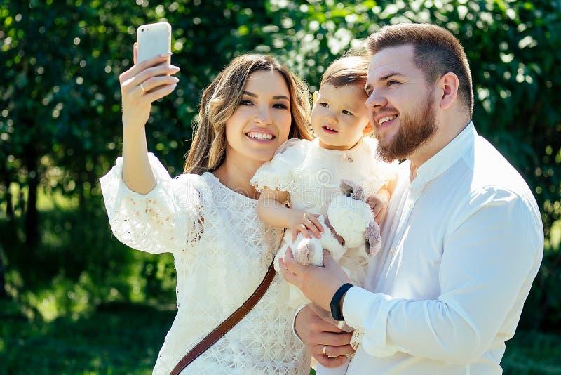 La familia es feliz y elegante y se puede caminar en verano en el parque. bella madre, padre elegante y linda hija foto de archivo libre de regalías