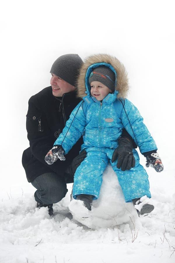 La familia esculpe el muñeco de nieve imagen de archivo