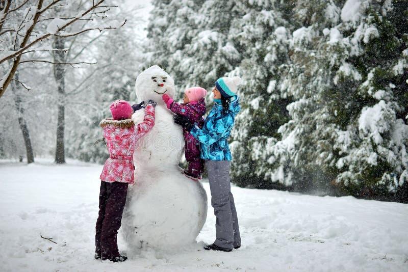 La familia esculpe un muñeco de nieve grande en el bosque en invierno imagenes de archivo