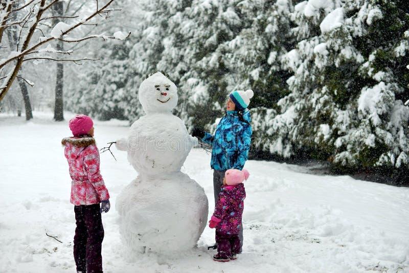 La familia esculpe un muñeco de nieve grande en el bosque en invierno fotografía de archivo