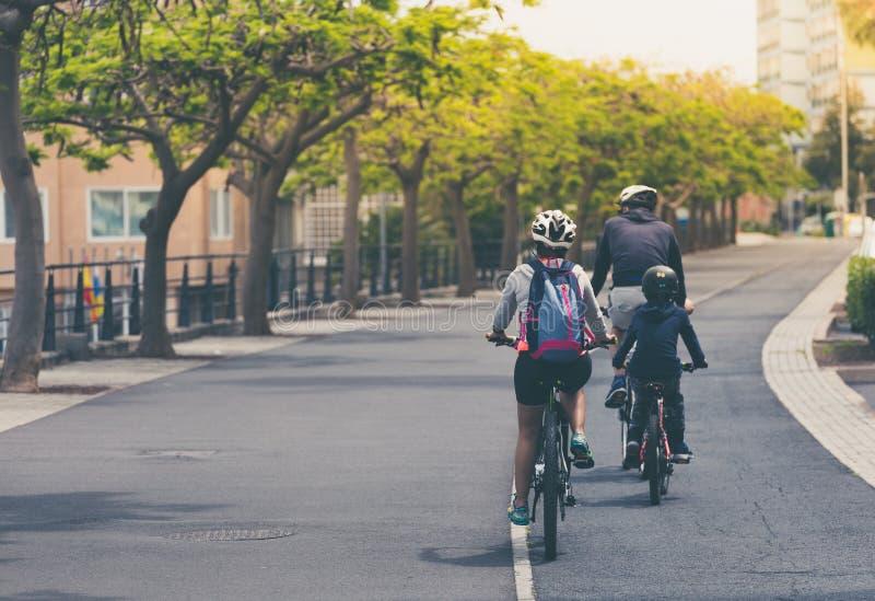 La familia está montando en las bicis en la trayectoria de la bicicleta foto de archivo libre de regalías