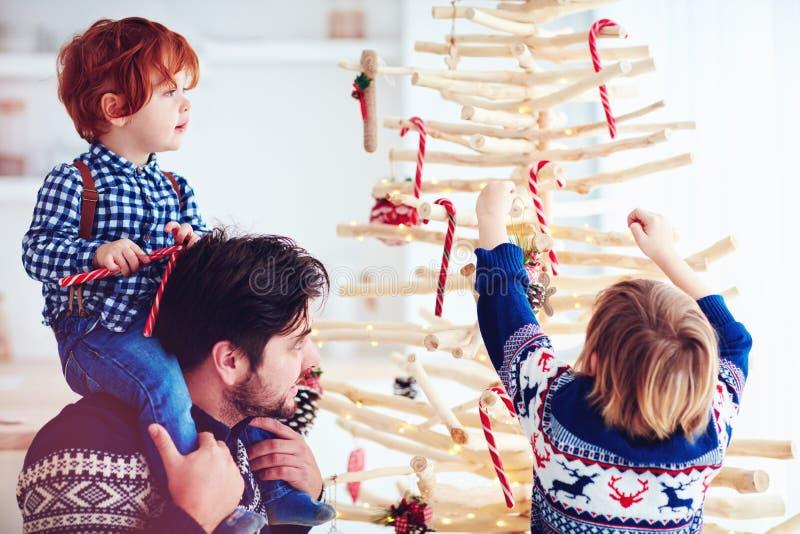 La familia feliz adorna un árbol de navidad extraordinario hecho de ramas y de madera de deriva en casa foto de archivo libre de regalías