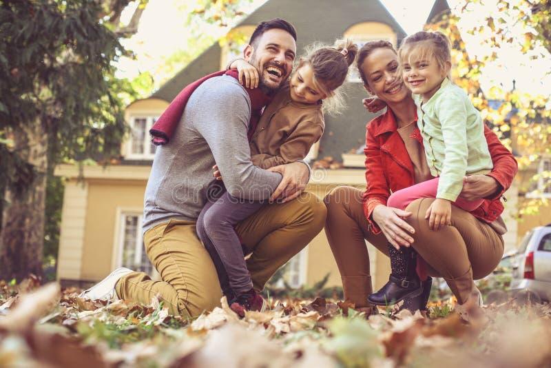 La familia feliz afuera en patio trasero colorido de la caída presenta a la cámara imagenes de archivo