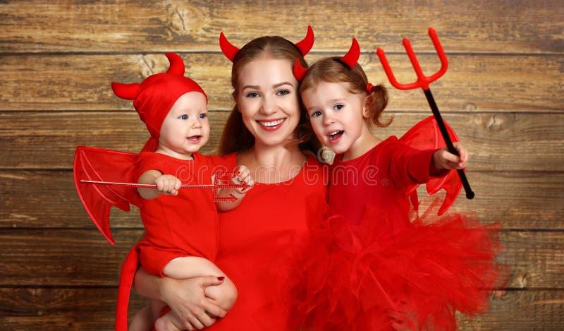 La familia feliz con el diablo de los trajes se prepara para Halloween imagen de archivo libre de regalías