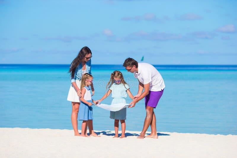 La familia feliz con el mapa encuentra la manera en la playa foto de archivo