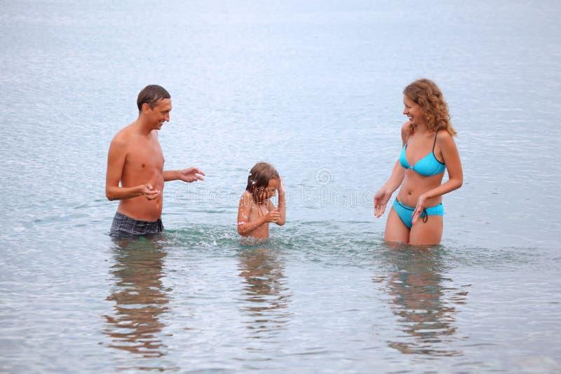La familia feliz con la muchacha salpica las manos del agua foto de archivo libre de regalías